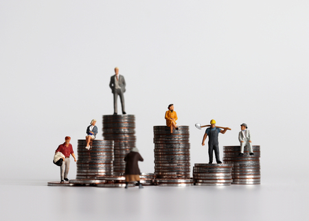 Coin piles and miniature people. The concept of difference between poverty and wealth. Stockfoto