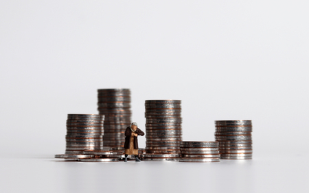 Coin piles and miniature woman. The concept of the poor. 스톡 콘텐츠