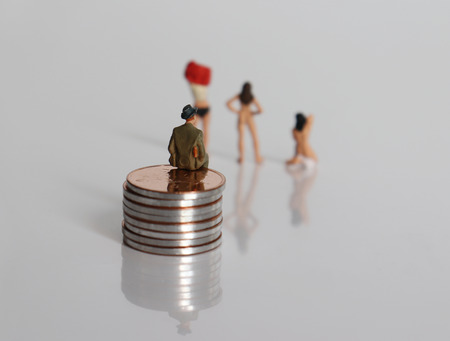 A miniature man sitting on a pile of coins, watching women undressing. A concept on the question of sex merchandising. Stock Photo - 117501132