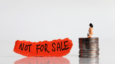 NOT FOR SALE message on the ripped paper. Stop selling people. Miniature women with the pile of coins. Stock Photo