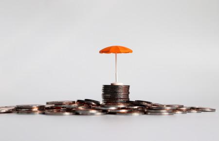 An orange umbrella on a pile of coins. Stock Photo