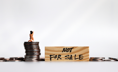 Not for Sale Concept. Coins and miniature women. Stock Photo