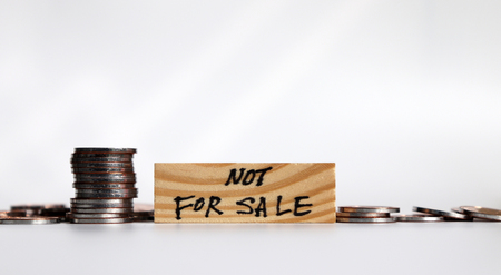Not for sale campaign. Coins and block of wood.