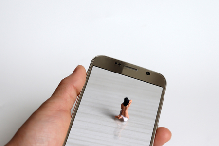 The back of a miniature woman who is changing their clothes. Miniature people and Smartphone. Stock Photo