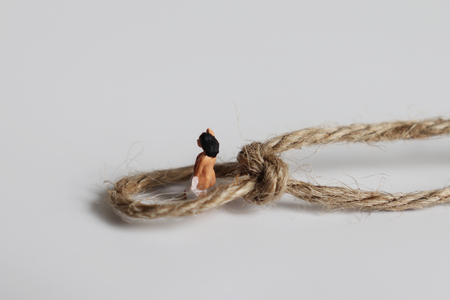 The concept of sexual repression. A miniature woman tied with a rope. Stock Photo