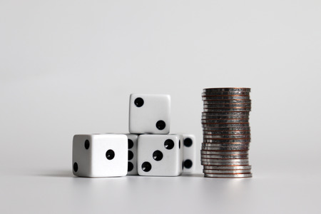 Dice and coins on a white background.