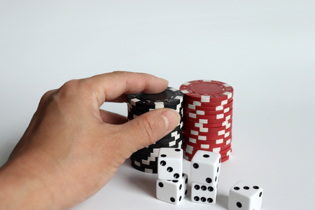 Casino chips and dice on a white background. The hand holding the chip.