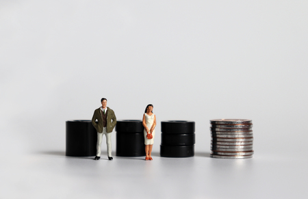 Equal labor equal pay concept. Miniature woman with a miniature man. Stock Photo