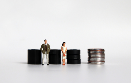 Equal labor equal pay concept. Miniature woman and a miniature man. Stock Photo