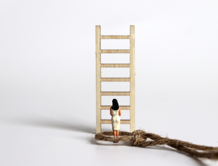 A miniature woman standing in front of a wooden ladder.