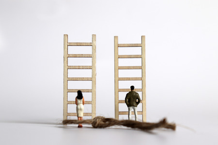A miniature woman and a miniature man standing in front of a wooden ladder. Stock Photo