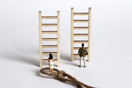 The back of a miniature woman and a miniature man standing in front of a wooden ladder. Stock Photo