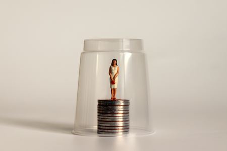 A glass ceiling concept. Miniature women and coins. Stock Photo