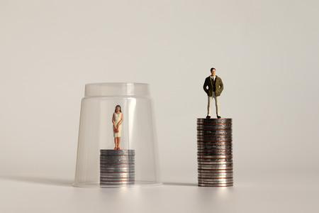 Un concepto de techo de cristal. Un hombre en miniatura y una mujer en miniatura de pie sobre un montón de monedas de diferentes alturas.