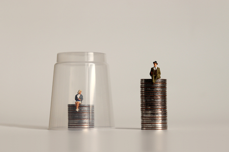 A glass ceiling concept. A miniature man and a miniature woman sitting on a pile of coins of different heights. Stock Photo