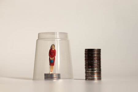 A glass ceiling concept. A miniature woman standing on a pile of coins.