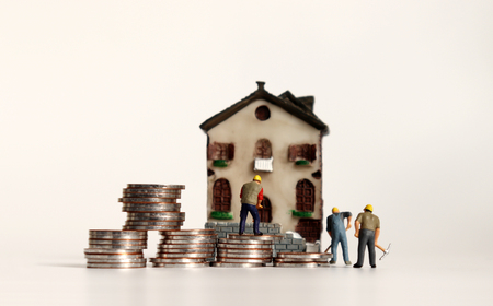 Miniature houses and miniature workers with coins. 版權商用圖片