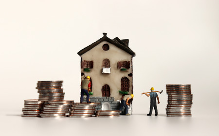 Miniature workers with a pile of coins in front of the miniature house.
