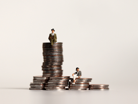 Miniature people sitting on a pile of coins. Business concepts.