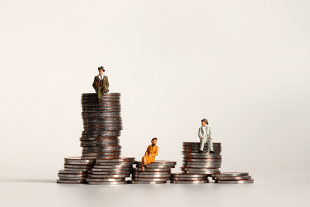 Miniature people sitting on a pile of coins. The concept of income distribution gaps. Stock Photo