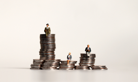 Miniature people sitting on a pile of coins. A concept of economic imbalances. Stock Photo
