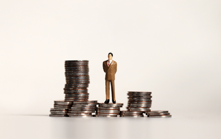 A pile of coins and a miniature businessman. Business concepts. Stock Photo
