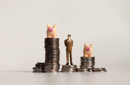 Miniature business man standing and pink piggy on a pile of coins.