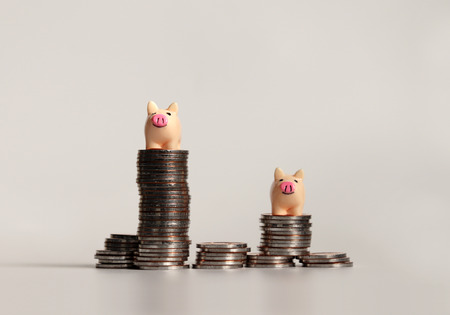 Two miniature pink piggy on top of pile of coins. Stock Photo