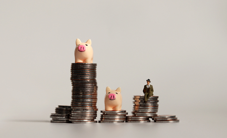 Two miniature pink piggy and a miniature man on pile of coins.
