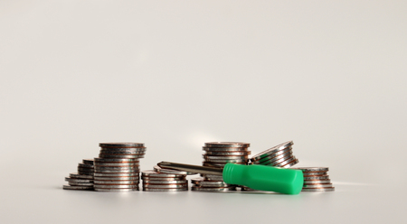 A mini screwdriver with a pile of coins. Stock Photo