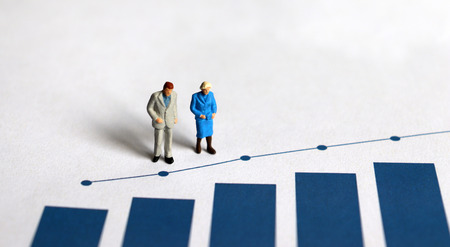 A miniature older people standing on a bar graph.