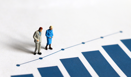 Una persona mayor en miniatura de pie sobre un gráfico de barras azul.