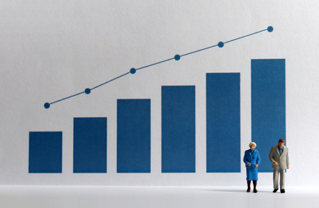 Blue bar graph with flow linear graph. Miniature older people. Stock Photo