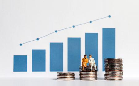 Grafico a barre blu con grafico lineare di flusso. La pila di monete e gli anziani in miniatura. Concetti sulla crescita della popolazione anziana e sul costo.