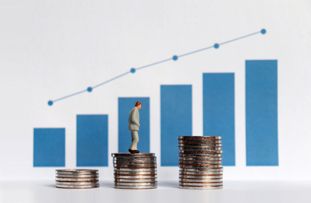 Blue bar graph with flow linear graph. The stack of coins and miniature older people. Concepts about increasing the population of the elderly and increasing the cost needed. Stock Photo