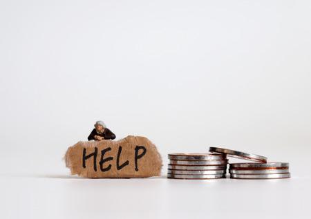 Le concept d'inégalité économique. Une lettre d'AIDE sur un morceau de papier déchiré avec une femme miniature. Personnes miniatures et pièces de monnaie.