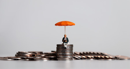 Stack of coins and a miniature people with an orange umbrella. Standard-Bild