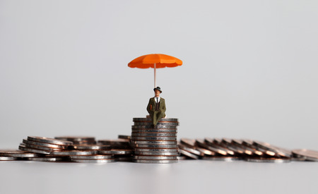 Pile de pièces et un peuple miniature avec un parapluie orange. Banque d'images