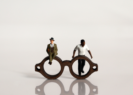Miniature people and miniature glasses. The concept of racial prejudice and discrimination.