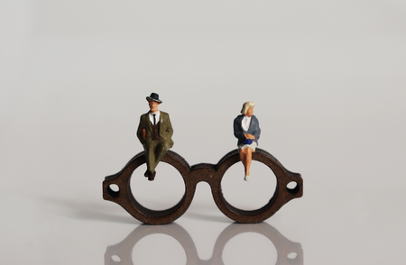 Miniature people and miniature glasses. The concept of stereotypes about masculinity and femininity demanded by society.