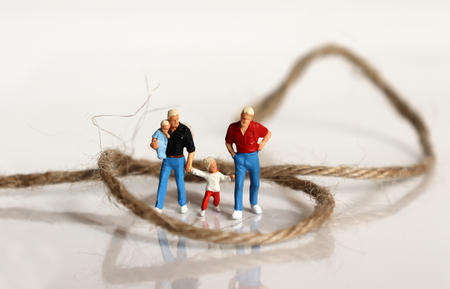 Miniature people and miniature glasses. The concept of social repression of gay families.