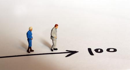 Ein Miniaturmann und eine Miniaturfrau, die auf die Nummer 100 zulaufen. Standard-Bild