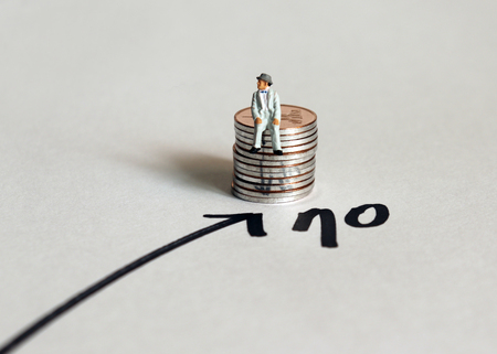 A miniature man sitting on a stack of coins next to the number 70. The concept of extending retirement age. Фото со стока