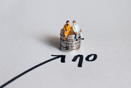 Miniature people sitting on a stack of coins next to the number 70. The concept of extending retirement age. Фото со стока