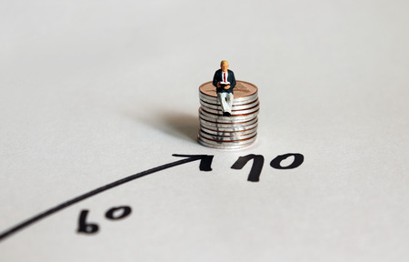 Miniature man sitting on a stack of coins next to the number 70.