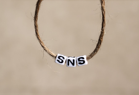 'SNS' alphabet white cube in a round rope.