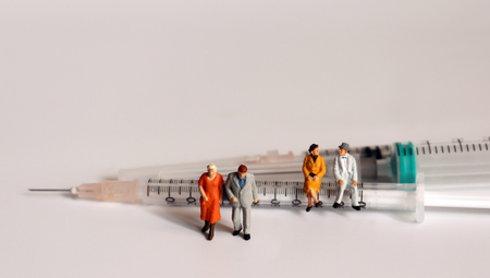 Miniature old age people and the syringe. The concept of disease management in the elderly.