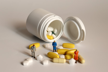 Miniature old age people and pills. Concepts on the importance of health care for the elderly.