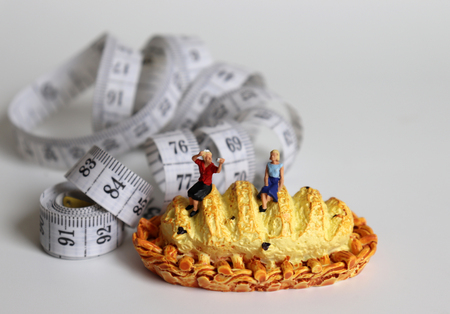 Miniature bread and white tape measure. Two miniature women sitting on a bread.