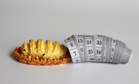 Miniature bread and white tape measure. Stock Photo